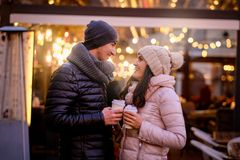 Happy romantic couple wearing warm clothes enjoying spending time together on a date in evening street near a cafe. Young romantic couple wearing warm clothes royalty free stock images