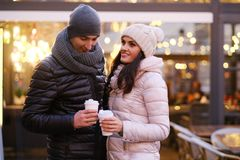 Happy romantic couple wearing warm clothes enjoying spending time together on a date in evening street near a cafe. Young romantic couple wearing warm clothes royalty free stock image