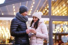 Happy romantic couple wearing warm clothes enjoying spending time together on a date in evening street near a cafe. Young romantic couple wearing warm clothes stock photos
