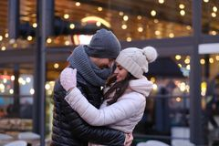 A young romantic couple wearing warm clothes hugging together in evening street near a cafe outside at Christmas time. Happy romantic couple wearing warm clothes stock image