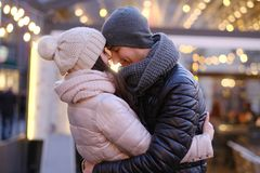 A young romantic couple wearing warm clothes hugging together in evening street near a cafe outside at Christmas time. Happy romantic couple wearing warm clothes stock photo