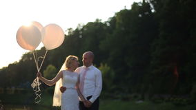 Happy romantic couple on wedding day. Bride and Groom with balloons on sunset in the field. stock video footage