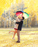 Happy romantic kissing couple in love with colorful umbrella together at warm sunny day over yellow leafs stock images