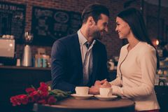 Happy romantic man and woman sitting in a cafe with flowers stock images