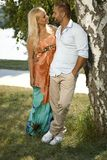 Happy romantic married couple standing in shade. Outdoor. Hand in pocket, embracing, smiling Stock Images