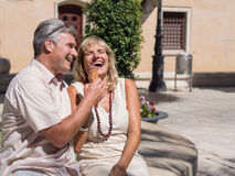 Happy romantic mature couple laughing at a good joke with ice cream. Happy romantic mature attractive middle-aged couple sitting on a stone wall in an urban Royalty Free Stock Photography