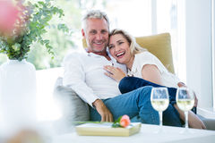 Happy romantic mature couple sitting on armchair. At home Stock Photo