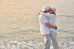 Couple in love hugging and kissing on the sandy beach in the sunset. Happy romantic middle aged couple in love hugging and kissing on the sandy beach in the royalty free stock photo