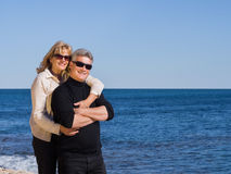 Happy romantic middle-aged couple at the sea. Standing in a close embrace smiling at the camera against a blue ocean with copyspace Stock Photo