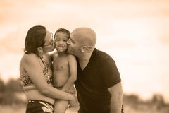 Happy and romantic mixed ethnicity couple Caucasian man and Asian Indonesian woman kissing their little son, the parents holding royalty free stock image