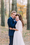 Happy romantic newly married couple embracing each other in the autumn pine forest Royalty Free Stock Photo