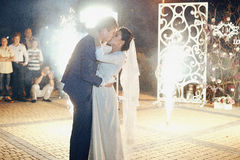 Happy romantic newlywed couple kissing at reception, fireworks b Royalty Free Stock Images