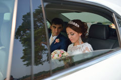 Happy romantic newlyweds, bride and groom sitting in wedding car Stock Photos
