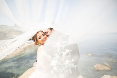 Happy and romantic scene of just married young wedding couple posing on beautiful beach Royalty Free Stock Image
