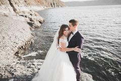 Happy and romantic scene of just married young wedding couple posing on beautiful beach.  Royalty Free Stock Image