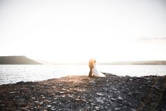 Happy and romantic scene of just married young wedding couple posing on beautiful beach.  stock images