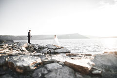 Happy and romantic scene of just married young wedding couple posing on beautiful beach.  Stock Photos