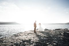 Happy and romantic scene of just married young wedding couple posing on beautiful beach Stock Image