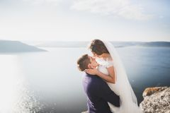Happy and romantic scene of just married young wedding couple posing on beautiful beach.  Royalty Free Stock Photo