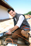 Happy roofer working on house stock photos
