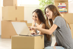 Happy roommates searching on line and moving home Stock Photos
