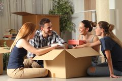 Happy roommates unboxing belongings moving home stock photography
