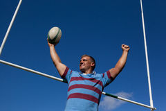 Happy rugby player holding ball with arms raised against blue sky. Low angle view of happy rugby player holding ball with arms raised by goal post against blue Stock Photography