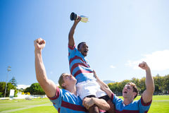 Happy rugby team enjoying victory while standing at field against sky. On sunny day stock photo
