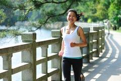 Happy runner. Healthy asian woman runner running in garden stock photos