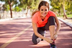 Happy runner tying her shoes Stock Images