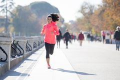 Happy runner woman in Autumn or Winter sportswear running and tr Stock Photos
