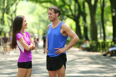 Happy runners couple talking after run in NYC park stock photo