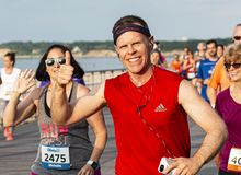Happy runners waving during a race on a boardwalk by the beach royalty free stock photos
