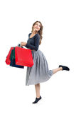 Happy running beautiful woman with many colorful shopping bags i Royalty Free Stock Images