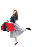 Happy running beautiful woman with many colorful shopping bags i Stock Photography