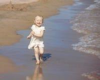 Happy running girl. Happy little girl run on the beach Stock Photography