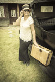 Happy 1920s Dressed Girl Holding Suitcase Next to Vintage Car royalty free stock photos