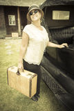 Happy 1920s Dressed Girl Holding Suitcase Next to Vintage Car Royalty Free Stock Photo