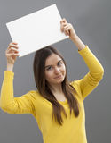 Happy 20s girl making an advertisement in raising a blank insert above her head Royalty Free Stock Images