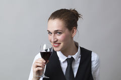 Happy 20s girl tasting red wine at party to celebrate success at becoming sommelier Royalty Free Stock Photo
