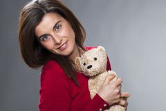 Happy 30s girl using the symbol of childhood for baby announcement. Childhood and tenderness concept - serene young brunette woman holding teddy bear next to Royalty Free Stock Images