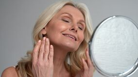 Happy 50s middle aged woman touching face skin looking in mirror.