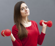 Happy 20s office girl holding dumb bells for toned arms and wellbeing Stock Photo