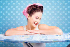 Happy 60s pinup housewife on blue ironing board Royalty Free Stock Image