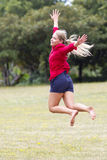 Happy 20s woman jumping high with happiness in sunny park Stock Image