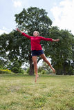 Happy 20s woman jumping for joy in sunny outdoors Stock Photography