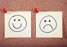 Happy and Sad Faces Pinned to a Noticeboard Stock Image