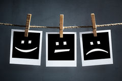 Happy, sad and neutral emoticons on instant print photographs. Happy, sad and neutral emoticons on instant print transfer photographs hanging on a clothesline Stock Photo