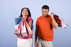 Happy and sad people at shopping. Couple at shopping  ,the young woman it is very happy and laughing with bags in her hands while the man it is sad,bored or Royalty Free Stock Photography