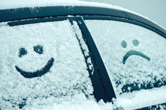 Happy and sad smiley emoticon face in snow. On car windows, winter season joy and happiness concept Royalty Free Stock Photos